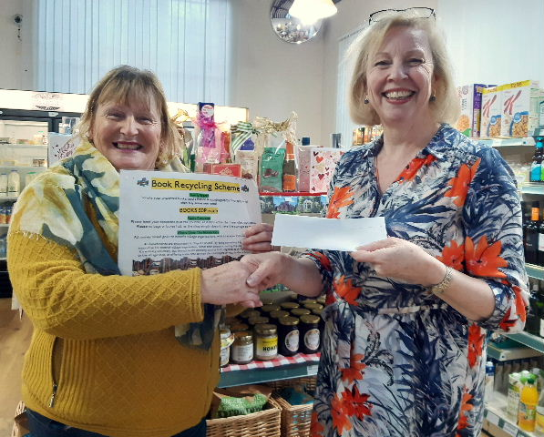 Anita Morris receives £50 from the Book Recycling Scheme's Linda Durno 28.01.20
